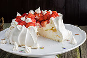 Sliced Pavlova Cake with Strawberries on White Plate on Old Wooden Table