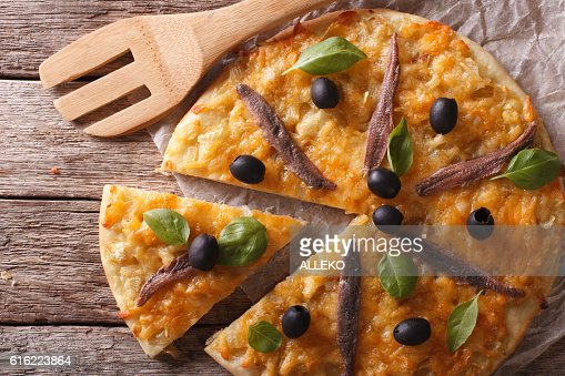 Sliced pizza with anchovies and onions close-up. horizontal top view : Stock-Foto