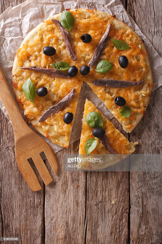 Sliced pizza with anchovies and onions. vertical top view : Stockfoto