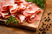 Sliced prosciutto on rustic wood table