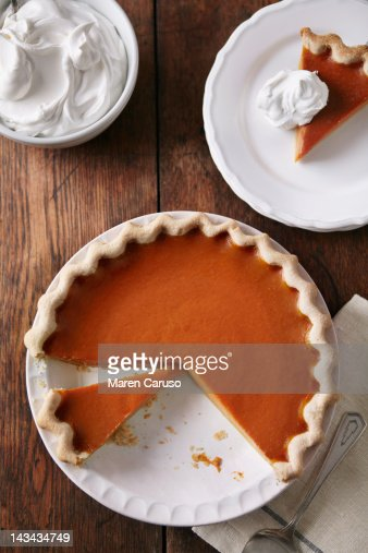 Sliced pumpkin pie on wood table from above stock photo
