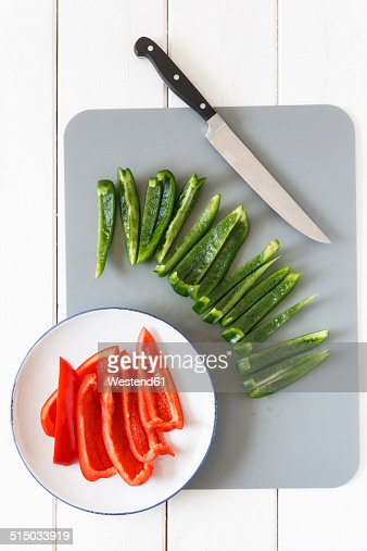 Sliced red and green ball peppers, knife and kitchen board, elevated view