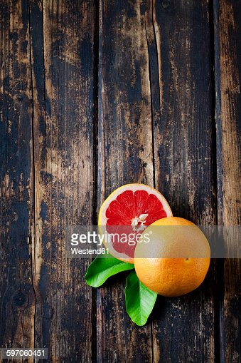 Sliced red grapefruit with leaves on dark wood