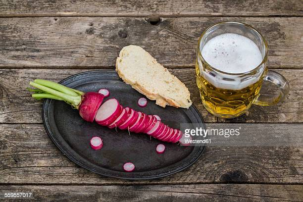 Sliced red radish and bread on metal tray and glass of beer