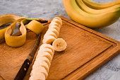 Sliced ripe banana with peeled on wooden background.