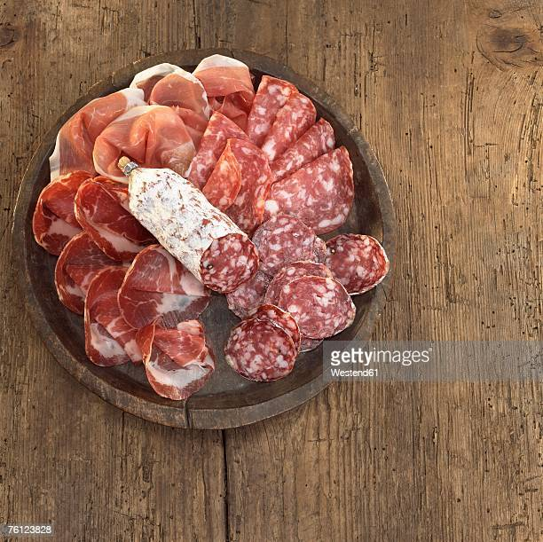 Sliced salami and ham on plate, overhead view