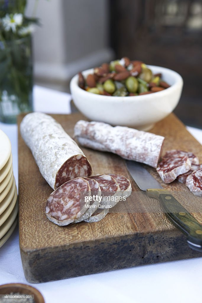 Sliced salami on cutting board with knife, bowl of olives in background, close-up : Stock Photo