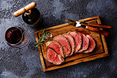 Sliced grilled tenderloin Steak roastbeef on wooden cutting board and Red wine on dark background