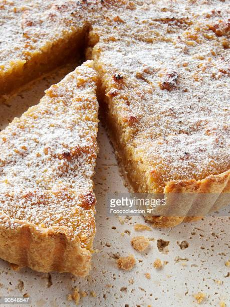 Sliced treacle tart dusted with powdered sugar, close up