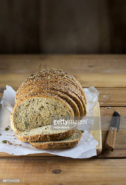 Sliced whole grain bread on wooden background.