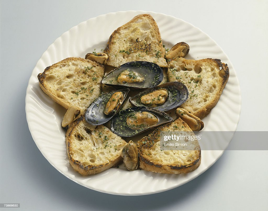 Slices of bread with oysters on plate : Stock Photo