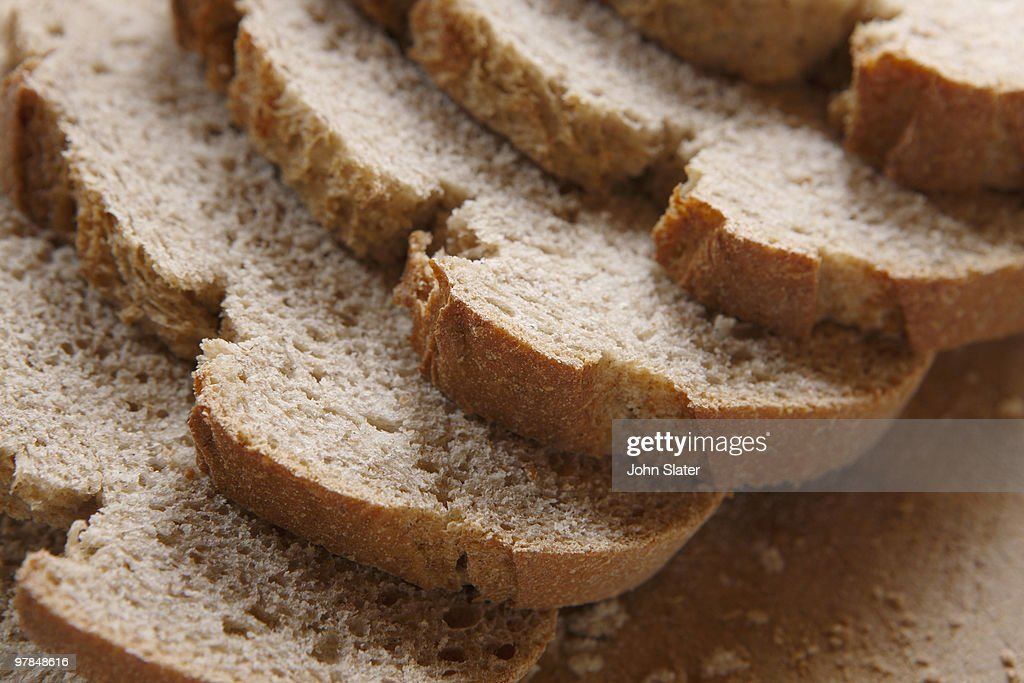 slices of brown bread on breadboard : Stock Photo