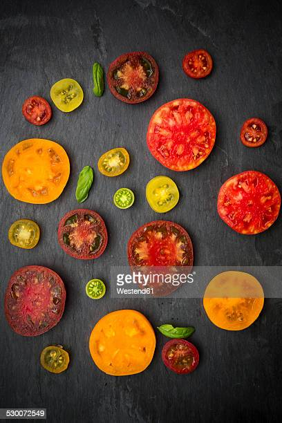Slices of different heirloom tomatoes on slate