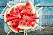 Slices of fresh juicy watermelon on a paper closeup on rustic wooden table