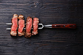 Slices of grilled meat barbecue steak Rib eye on meat fork on burned black wooden background