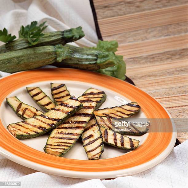 Slices of grilled zucchini on an orange and white plate