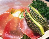 Slices of ham and melon in bowl, high angle view, close up, differential focus
