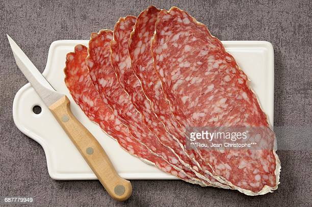 Slices of large dried sausage on a chopping board
