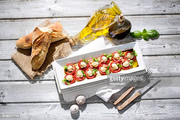 Slices of mozzarella cheese, tomatoes and basil herb on white plate