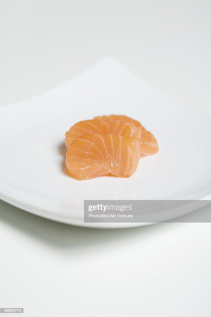 Slices of salmon sashimi on sushi plate