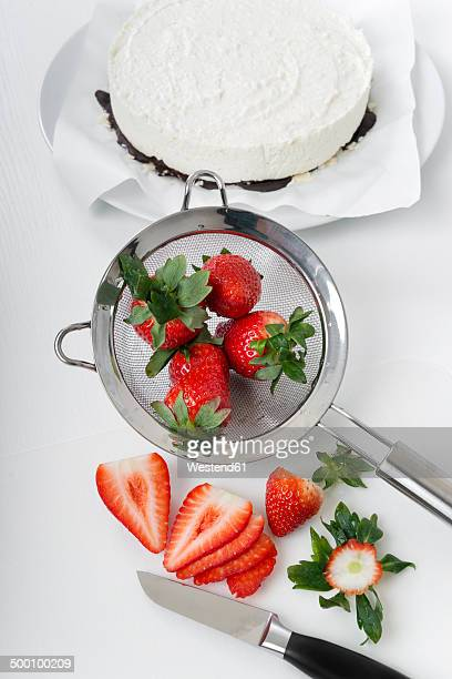 Slices of strawberries, kitchen knife and strainer on white ground, elevated view