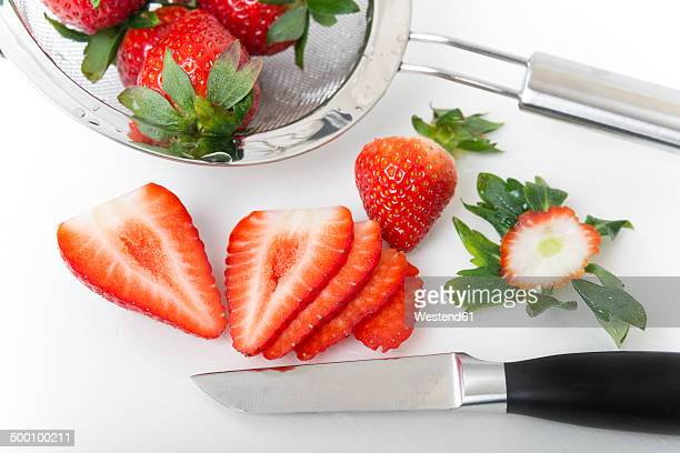 Slices of strawberries, kitchen knife and strainer on white ground