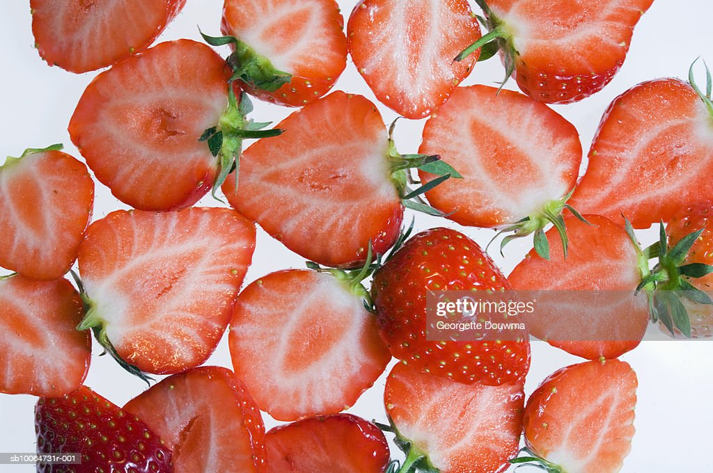 Slices of strawberries on white surface : Stock Photo