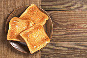 Slices of toasted bread in plate on wooden table, top view. Space for text