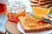 Slices of toasted bread with orange jam and glass jar for breakfast