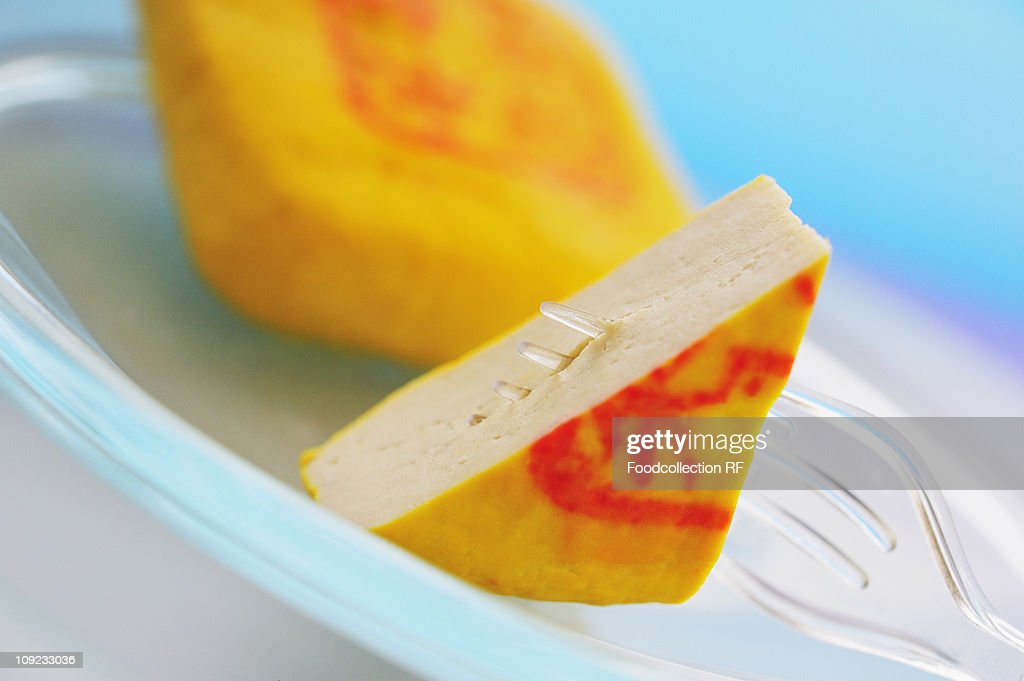 Slices of tofu with fork on plate, close-up : Stock Photo