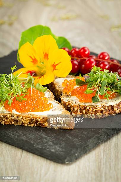 Slices of wholemeal bread with butter and red caviar on slate