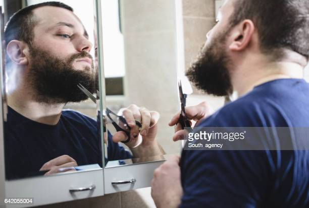 Slicing beard with scissors in the bathroom