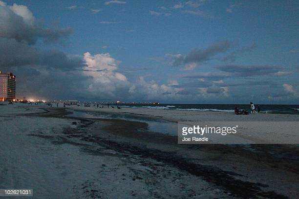 A slick of oil is seen on the beach after it washed ashore from the Deepwater Horizon oil spill in the Gulf of Mexico on July 4 2010 in Gulf Shores...