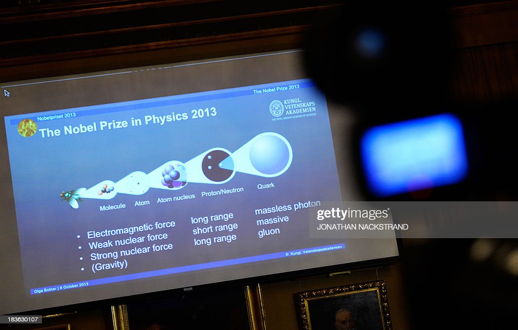 A slide on the screen explaining the work of British theoretical physicist Peter Higgs and Belgian theoretical physicist Francois Englert can be seen after the Swedish Royal Academy of Sciences committee announced them as the laureates the 2013 Nobel Prize in Physics during a press conference on October 8, 2013 at the Nobel Assembly at the Royal Swedish Academy of Sciences in Stockholm. NACKSTRAND