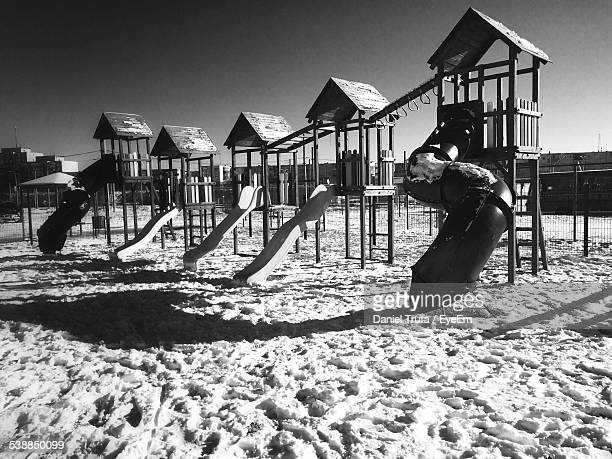 Slides On Snow Covered Playground Against Sky