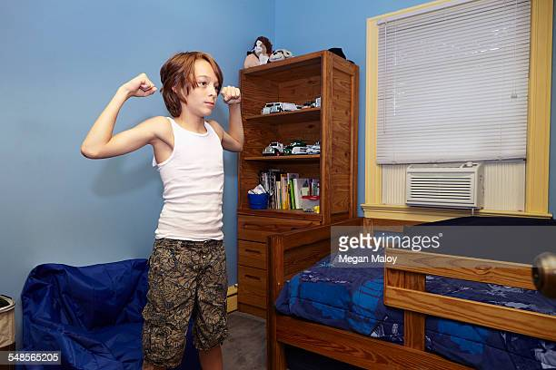 Slim boy flexing arm muscles in bedroom