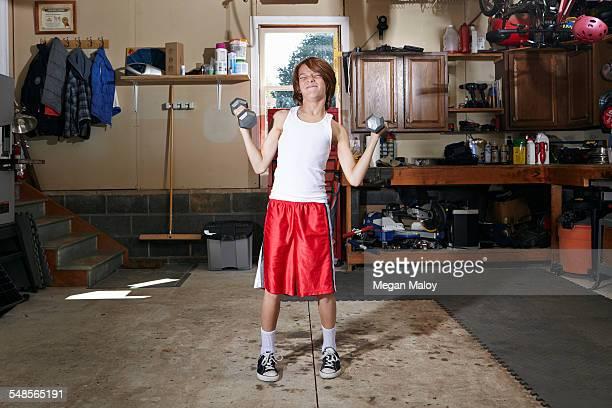 Slim boy struggling to lift hand weights in garage