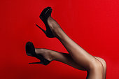 Slim female legs in dark stockings wearing high heels . red background