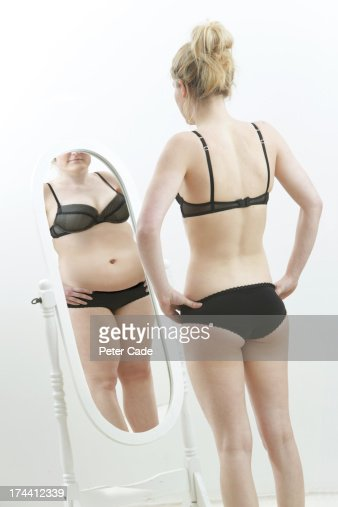 Slim girl looking at fat reflection in mirror : Stock Photo