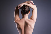 Slim topless woman on gray background, beauty female back, rear, view