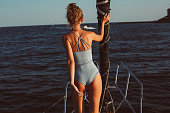 back view of slim young lady wearing blue one-piece swimsuit, thin waist, fair hair in bun, on the deck of the yacht