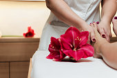 Masseur holding beautiful slim woman legs. Spa decorating with oriental flowers and wooden pieces