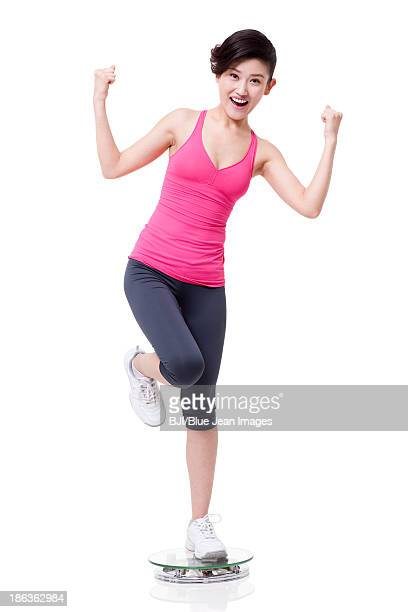 Slim young woman standing on scale and cheering