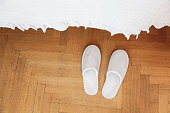 White slippers on a wooden floor in bedroom.