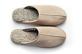 Closeup of a pair of men's slippers on a white background with shadows from above.