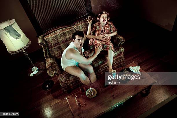 Slob couple watching television with pregnant woman in labor