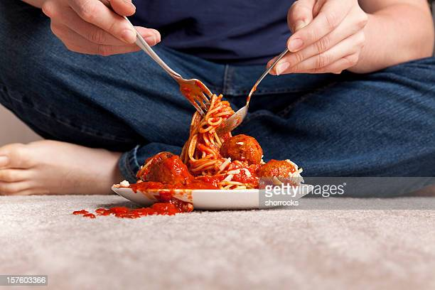 Slob eat spaghetti and meatballs sitting on a carpeted floor