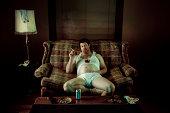Slob Man watching television while smoking in underwear