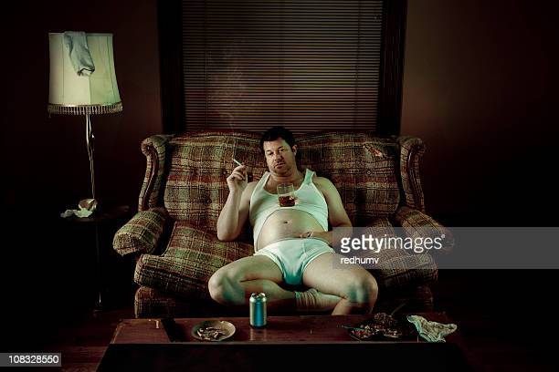 Slob Man watching television while smoking in underwear