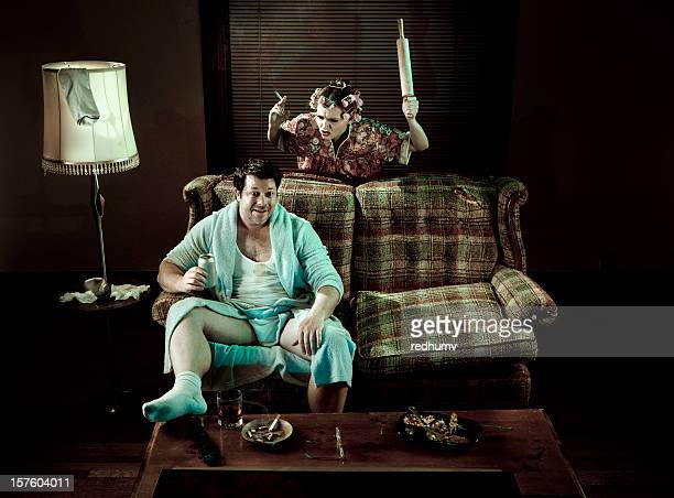 Slob Man watching television while smoking woman waves rolling pin